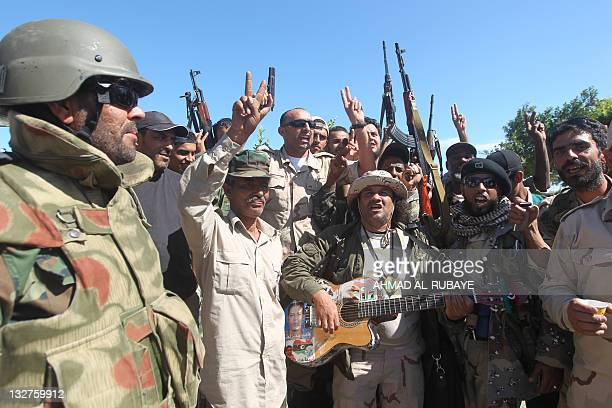 Libyan National Transitional Council fighters sing along during a lull in fighting against proMoamer Kadhafi gunmen in central Sirte on October 15 as...