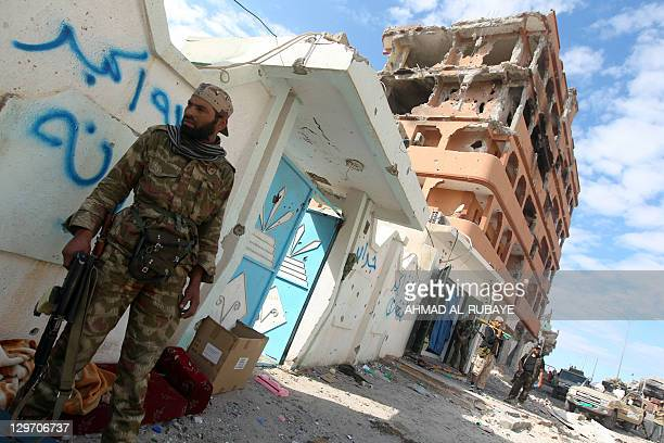 Libyan National Transitional Council fighters stand guard on October 19 2011 in front of damaged buildings hit by a rockets during continuing...