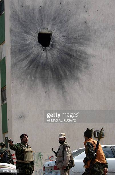 Libyan National Transitional Council fighters stand on October 19 2011 outside a building hit by a rocket in Sirte's neighbourhood Number 2 one of...
