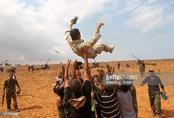 Libyan National Transitional Council fighters throw a comrade in the air as they rejoice after firing dozens of shells towards Sirte from the city's...