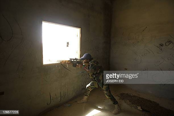 A Libyan National Transitional Council sniper monitors on September 25 2011 the frontline on the outskirts of the desert city of Bani Walid one of...