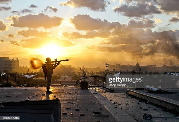 Libyan NTC fighter fires his rocketpropelled grenade toward buildings in District Two of Colonel Gaddafi's home city of Sirte on October 11 2011 in...