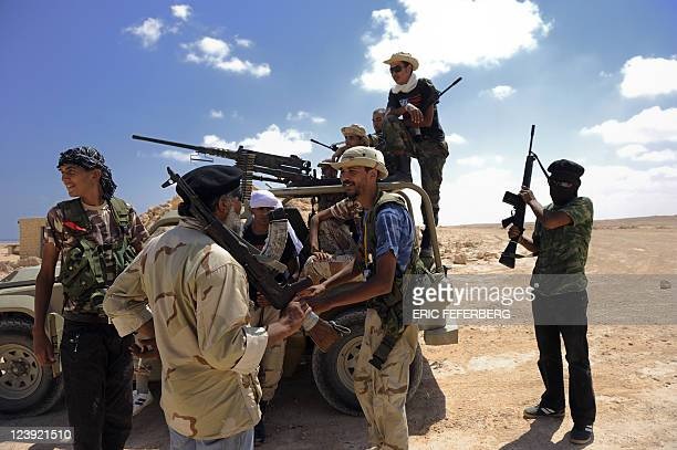 Libyan NTC fighters of the Zintan Martyrs' Brigade patrol in the desert near the town of Bin Jawad, east of Sirte, as they look for Kadhafi loyalists...