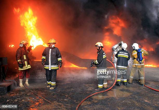 Libyan oil workers try to extinguish flames for the third day at an oil facility in northern Libya's Ras Lanouf region on January 23 after it was set...