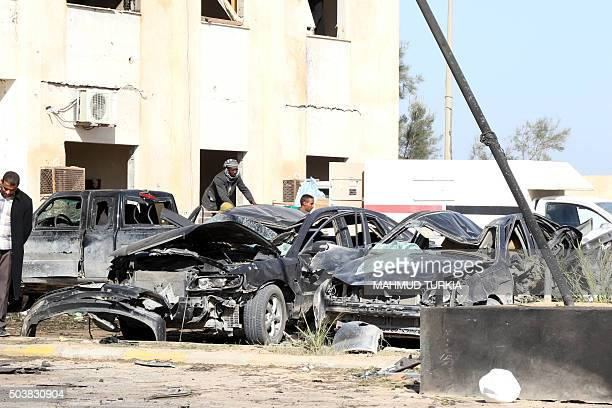 Libyan onlookers inpect damaged cars at the site of a suicide truck bombing on a police school in Libya's coastal city of Zliten some 170 kilometres...