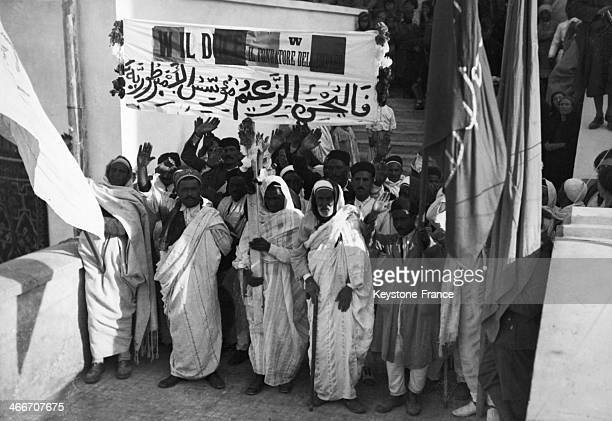 Libyan people and on the foreground Arab chiefs and their flags greeting the Duce Benito Mussolini during his visit in Libya on March 15 1937