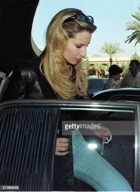 Libyan president's daughter Aisha alKadhafi steps into the back seat of her car while holding a rosary between her fingers 22 October 2000 in Baghdad