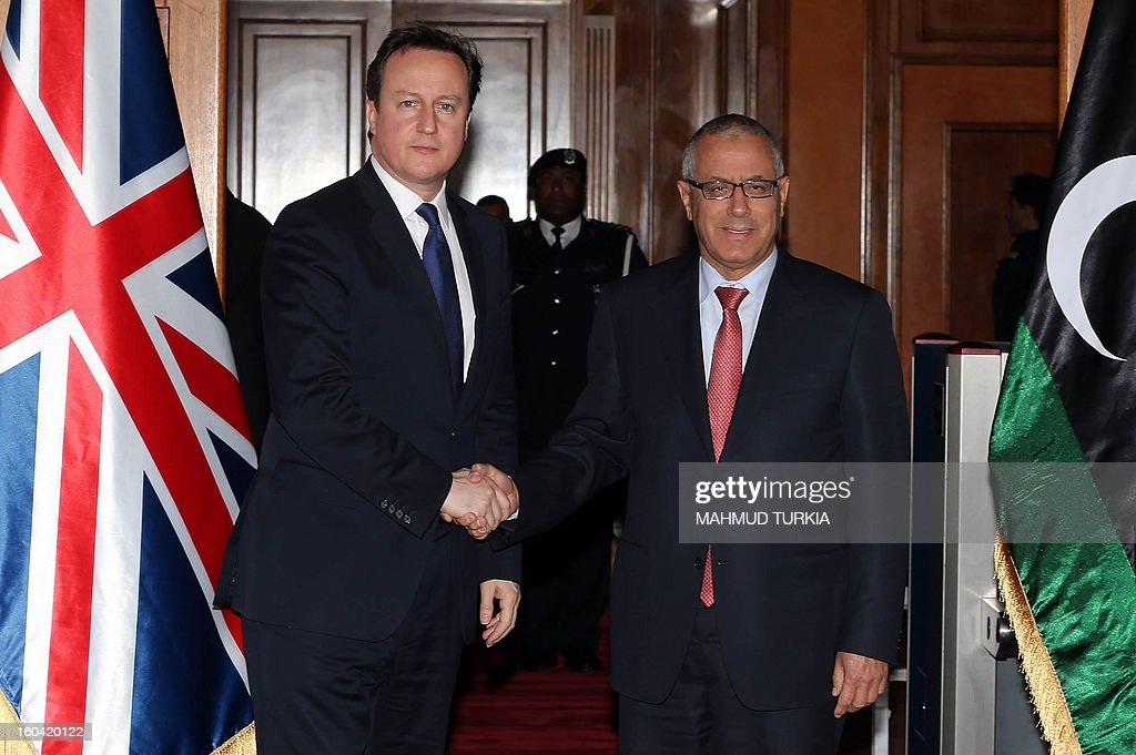 Libyan prime minister Ali Zaidan (R) greets British Prime Minister David Cameron (L) ahead of their meeting as part of the British PM visit in Libya on January 31, 2013 in Tripoli