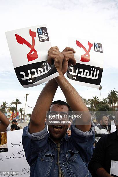 Libyan protester shout slogans as he holds placards in Martyrs Square during a protest against an extended mandate of the General National Congress...