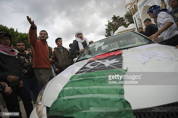 Libyan protesters gather around a car decorated with Libya's old national flag during a protest in the eastern Libyan town of Derna between Tobruk...