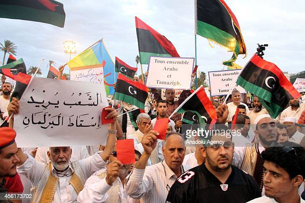 Libyan protesters hold placards and wave flags of Libya during a rally at the central Martyr's Square in Tripoli capital city of Libya in support of...