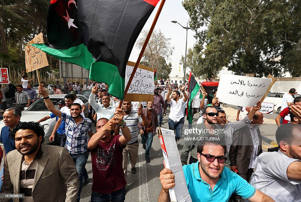 Libyan protesters wave banners and their new national flag as they demonstrate outside the Libyan General National Congress in support of the 'Political Isolation Law' which calls for the expulsion of former regime employees from top government and political posts on April 30, 2013 in Tripoli. Armed men demanding the expulsion of former officials of the regime of ousted Libyan leader Moamer Kadhafi surrounded the justice ministry in the capital, widening a campaign that began on the weekend with a siege on the foreign ministry, an official said.