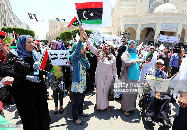 Libyan protesters wave national flags and hold placards during a demonstration on the Algeria Square to demand the removal of arms and the evacuation...
