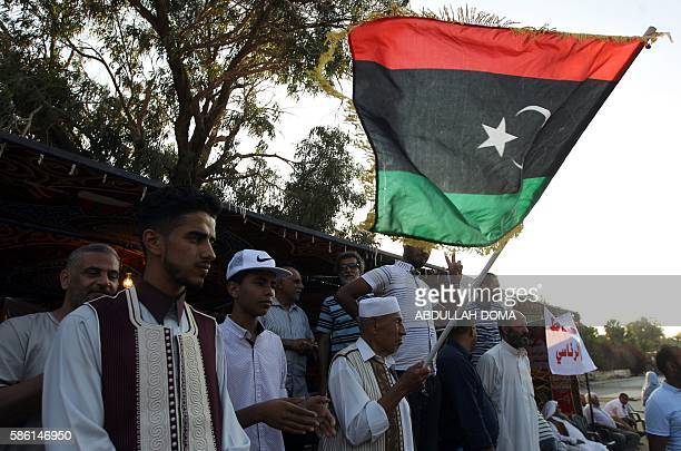A Libyan protestor waves his national flag during a demonstration in Benghazi in support of General Khalifa alHaftar who is aligned with the elected...