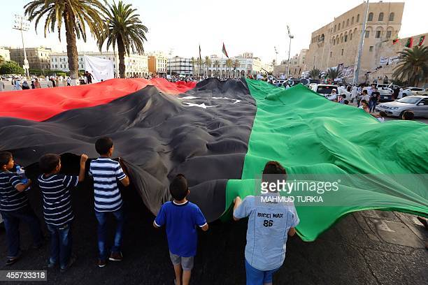 Libyan protestors wave a giant national flag during in a rally in Tripoli's central Martyr's Square on September 19 2014 in support of 'Fajr Libya' a...