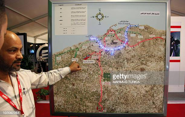 Libyan railway authority officials look at an underground map during the Libya Railways 2010 exhibition held in the capital Tripoli on June 14 as the...