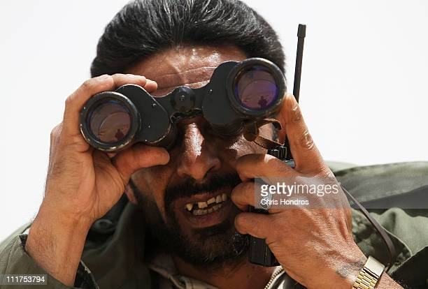 Libyan rebel commander looks through binoculars as he talks on a radio near frontline positions outside of Brega Libya April 6 2011 Rebel militias...