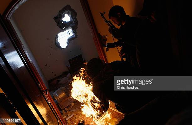 Libyan rebel fighter rolls a burning tire into a room containing ensconced government loyalist troops who were firing on them during housetohouse...