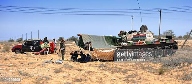 Libyan rebel fighters rest under a makeshift tent with their Russian T55 tank on the outskirts of the village of Umm Qandil village near the front...