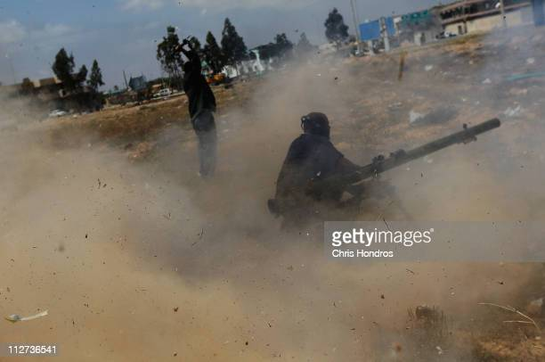 Libyan rebel forces fire a heavy rocket propelled grenade at a building holding government loyalist troops during street fighting on Tripoli Street...
