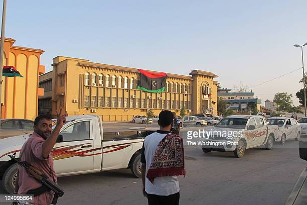 Libyan rebel gives the V for victory sign in the town of alAjelat in western Libya while the rebel flag is draped over a government building in the...