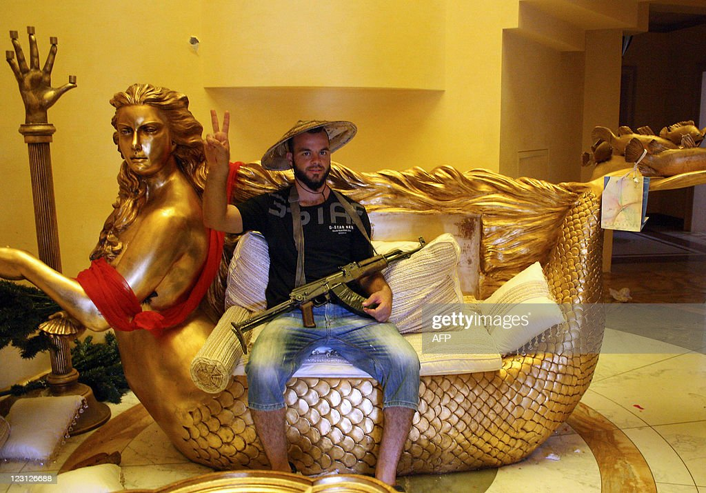 A Libyan rebel poses on a golden mermaid : News Photo