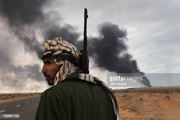 Libyan rebel scans the frontline as a facility burns on the frontline on March 9 2011 near Ras Lanuf Libya The rebels pushed back government troops...
