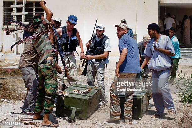 Libyan Rebel soldiers loot weapons from an exGaddafi military compound as they advance their position towards proGaddafi loyalists on August 26 2011...