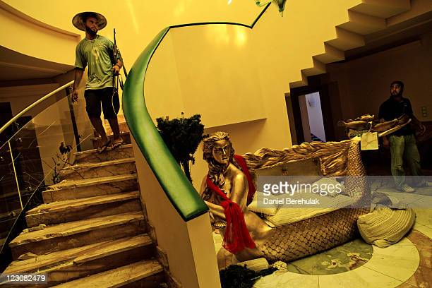 Libyan rebel soldiers walk through the house of Aisha Gaddafi the daughter of Libyan leader Muammar Gaddafi on August 30 2011 in Tripoli Libya Libyan...