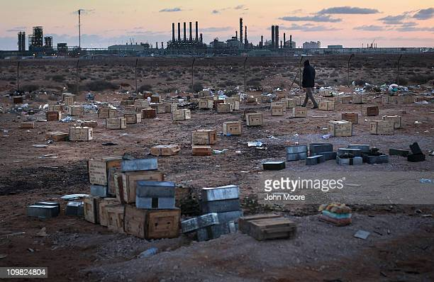 Libyan rebel walks through a field of ammunition near the strategic petroleum facilities on March 7 2011 in Ras Lanuf Libya Opposition forces...