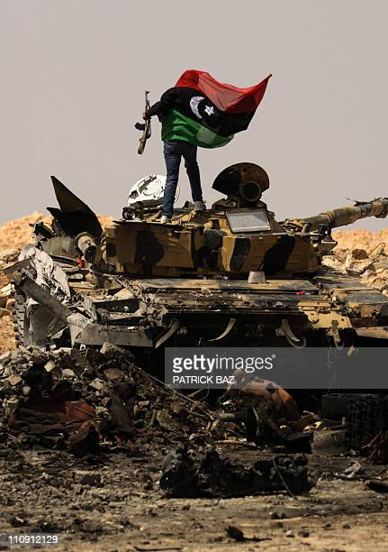 A Libyan rebel waves the rebellion flag on a loyalist army tank at a site bombed by coalition air force in the town of Ajdabiya on March 26 2011 as...
