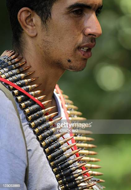 A Libyan rebel with a bullet belt around his neck patrols a street in Tripoli on August 30 2011 Libya's rebels issued an ultimatum for Moamer...