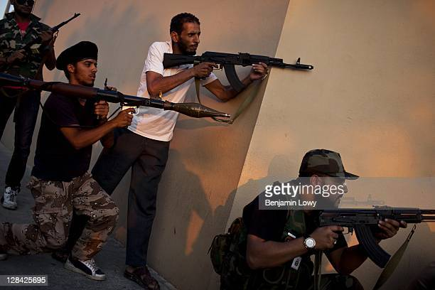 Libyan Rebels aim their weapons at a suspected Gaddafi loyalist sniper who targeted the Corninthian hotel home to a large cadre of international...