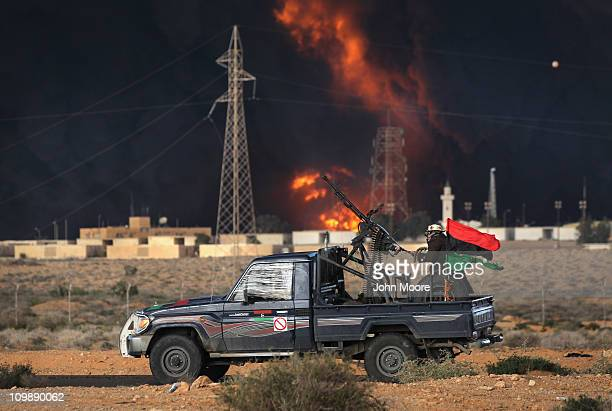 Libyan rebels attack government troops as a facility burns on the frontline on March 9 2011 near Ras Lanuf Libya The rebels pushed back government...
