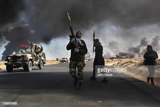 Libyan rebels battle government troops as smoke from a damaged oil facility darkens the frontline sky on March 11, 2011 in Ras Lanuf, Libya....