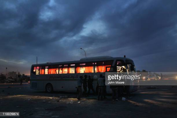 Libyan rebels board a bus to take them away from the frontline on March 12, 2011 near Brega, Libya. Opposition forces have been losing ground as...