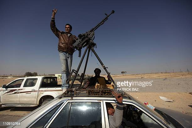 Libyan rebels celebrate in the town of Ajdabiya on March 26, 2011 as forces loyal to Libyan leader Moamer Kadhafi were retreating after rebels...