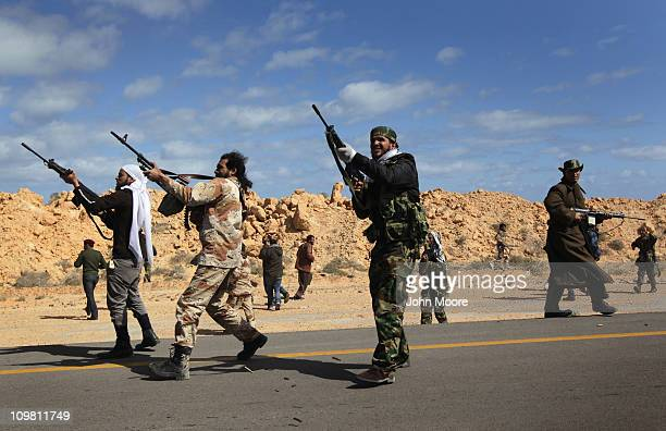 Libyan rebels fire during a government helicopter attack on the frontline on March 6, 2011 near Ben Jawat, Libya. Rebels lost territory as troops...