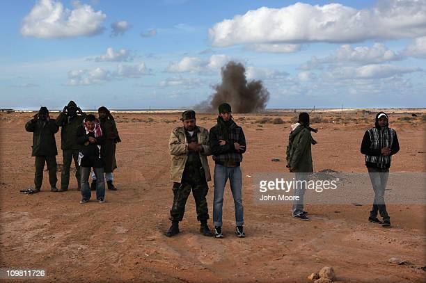 Libyan rebels pray as a government bomb explodes behind them on the frontline on March 6, 2011 near Ben Jawat, Libya. Rebels lost territory as forces...