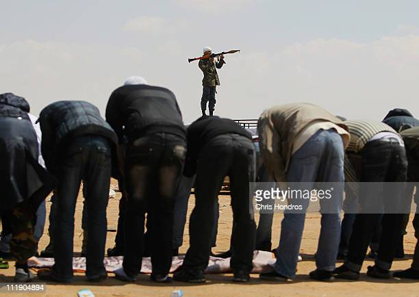 Libyan rebels pray while a comrade stands with a rocket propelled grenade launcher on the western edge of Ajdabiyah April 8 2011 in Ajdabiyah Libya...