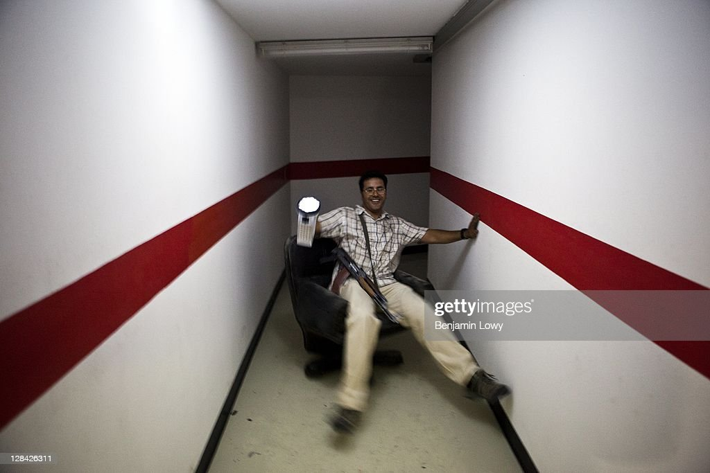 A Libyan rebels rides a wheeled office chair through secret underground tunnels in the looted and NATO bombed home of former Libyan dictator Moammar Gaddafi's son Motasem, on September 2 2011 in Tripoli, Libya.