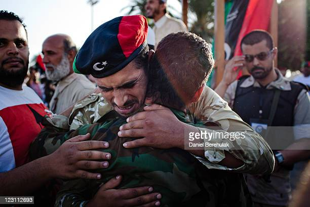 Libyan rebels soldiers embrace as they grieve at Martyr Square formerly known as Green Square, for the Eid Al-Fitr prayer on August 31, 2011 in...