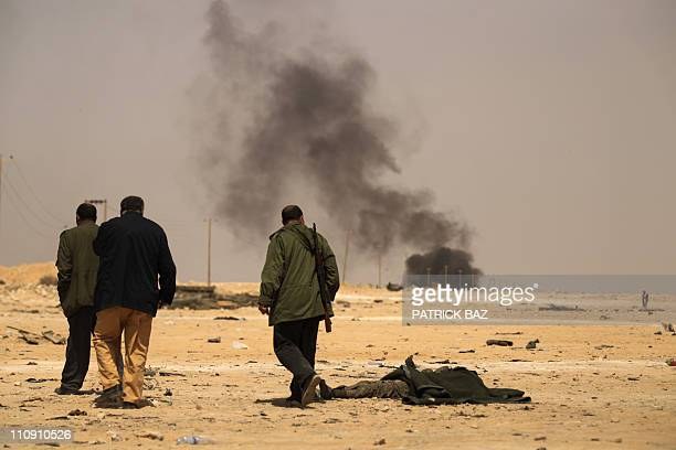 Libyan rebels walk past the bodies of loyalist fighters on a coalition bombed site in the town of Ajdabiya on March 26 as forces loyal to Libyan...