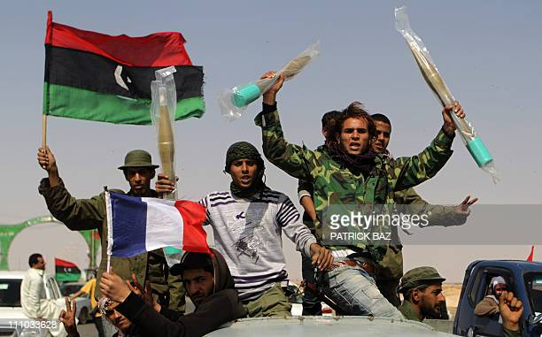 Libyan rebels waving the French and rebellion flags raise brand new rocket propeled grenades they took from abandonned progovernment forces...