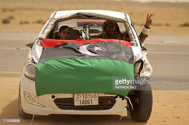 Libyan rebels with a SAM7 sitting on the backseat drive a wrecked car decorated with Libya's former national flag in Ajdabiya on March 14 2011 as...