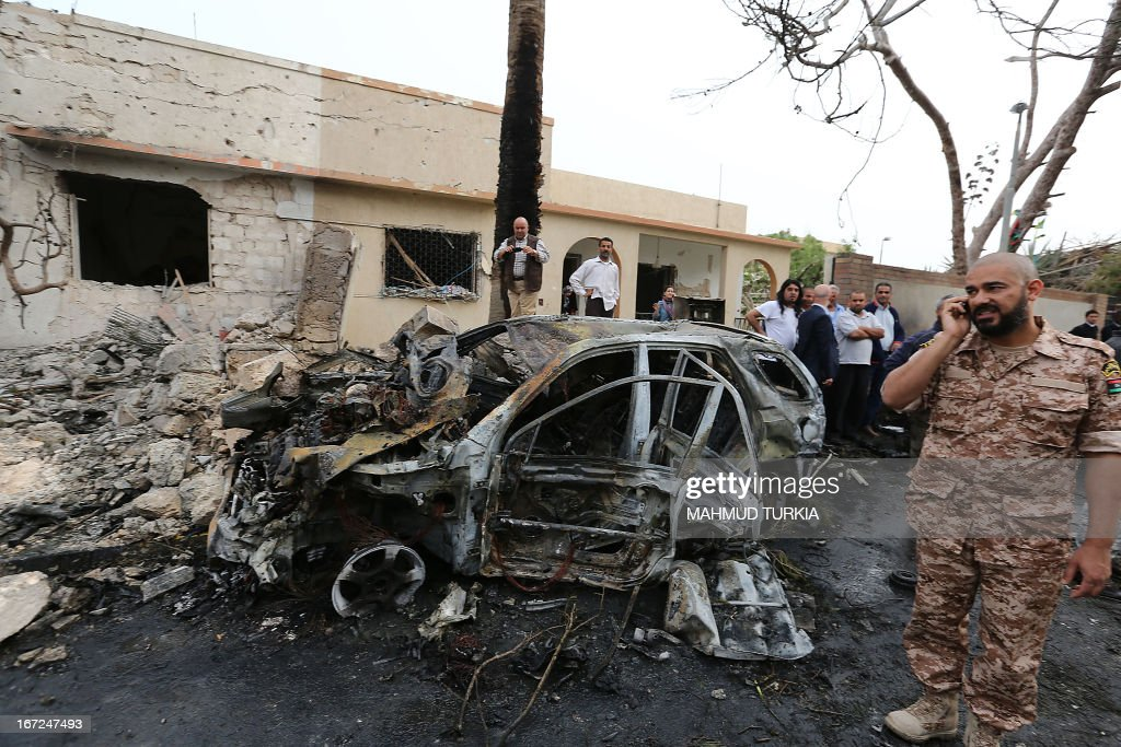 Libyan security forces and civilians gather across the street from the French embassy in Tripoli following a car bomb blast, on April 23, 2013. A car bomb blasted the embassy of France in Tripoli, injuring two French guards and causing serious damage to the building, embassy and Libyan sources said.