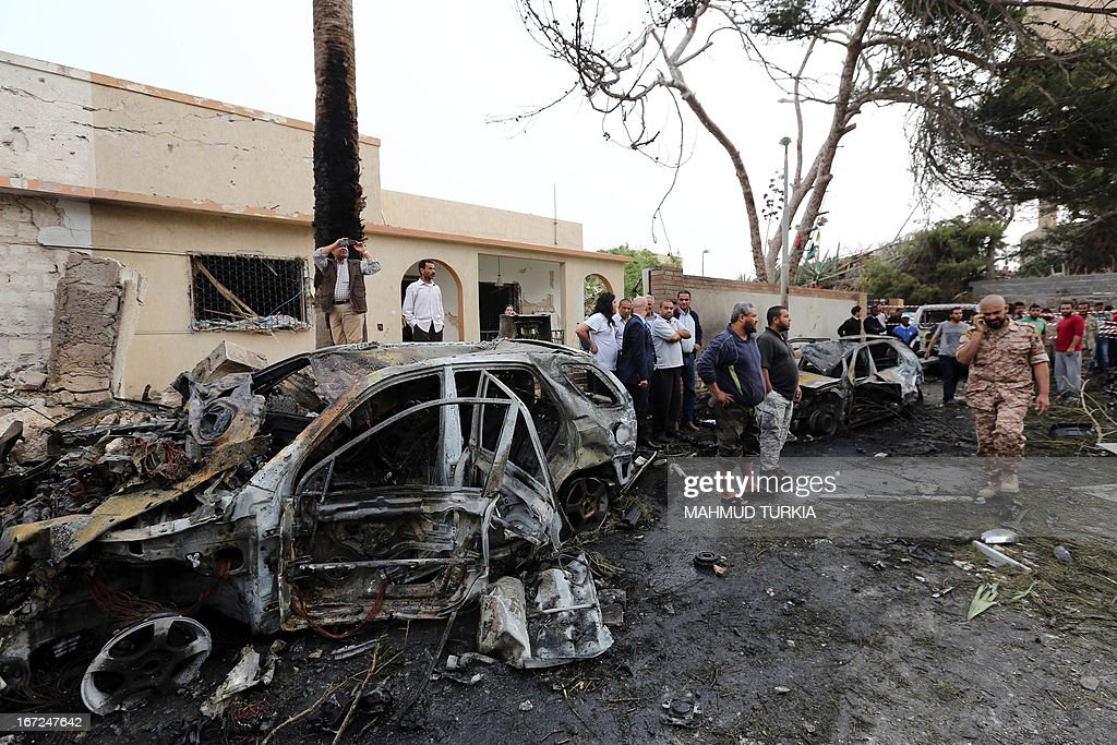 Libyan security forces and civilians gather outside across the street from the French embassy in Tripoli following a car bomb attack, on April 23, 2013. A car bomb blasted the embassy of France in Tripoli, injuring two French guards and causing serious damage to the building, embassy and Libyan sources said.