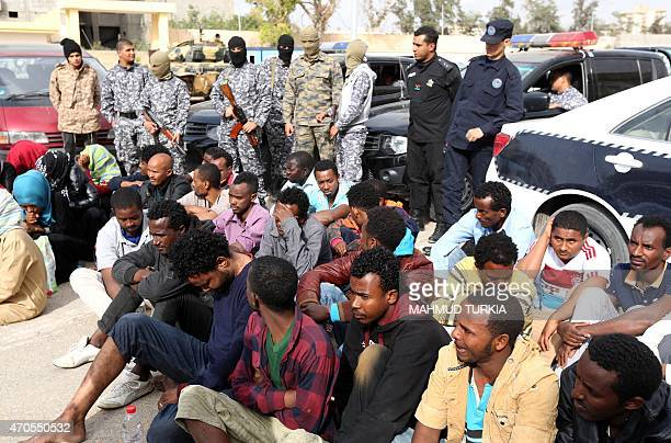 Libyan security forces guard migrants who were detained in Tripoli's western neighborhood of Ghut alShaal on April 21 as they were gathering to...