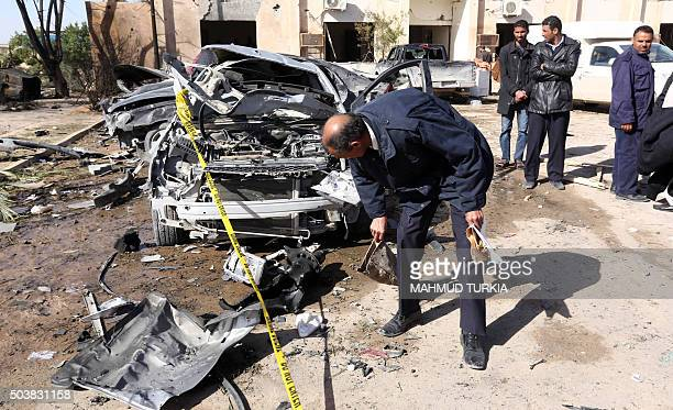 Libyan security forces inpect damaged cars at the site of a suicide truck bombing on a police school in Libya's coastal city of Zliten some 170...
