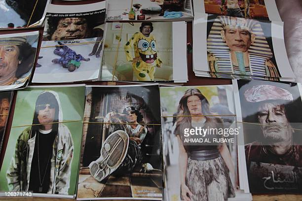A Libyan street vendor displays posters and stickers mocking Moamer Kadhafi at a stall in Tripoli's Marty's Square on September 25 as hundreds of...